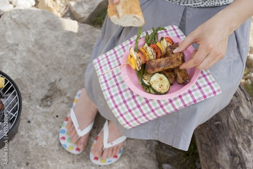 Woman eating grilled food and baguette on river bank
