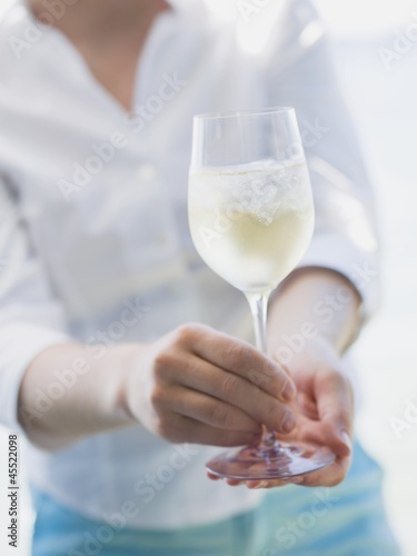 Woman holding glass of white wine with ice cubes out of doors