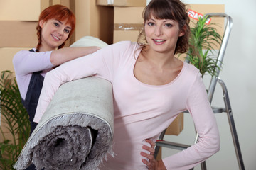 Young women carrying a rolled-up rug on moving day