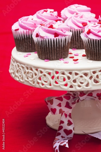 Chocolate cupcakes with pink icing on cake stand