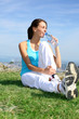 Runner sitting in nature with bottle of water