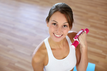 Fitness girl lifting dumbbells in gym