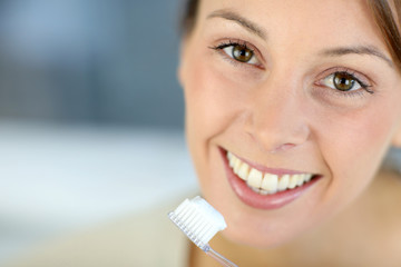 Closeup on woman's toothy smile brushing her teeth
