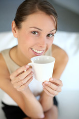 Attractive woman relaxing in sofa with cup of tea