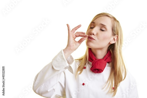 Blond female chef blowing a kiss
