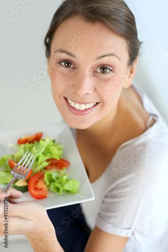 Closeup of cheerful woman eating fresh salad