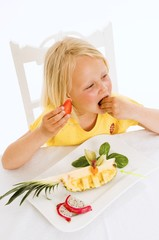 Girl eating fruit from plate