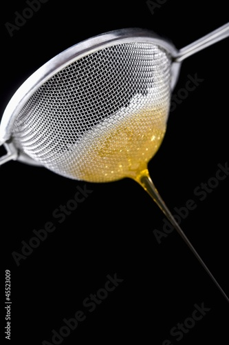 Honey running through sieve