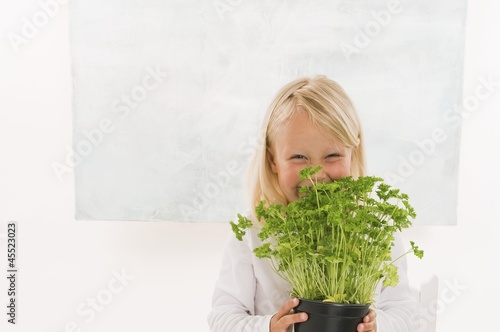 Girl holding a pot of parsley