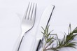 Knife and fork beside rosemary sprig