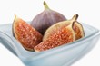 Fresh figs (whole, halved and quartered) in blue glass bowl