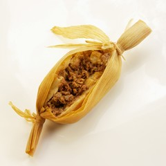 One Meat Filled Tamale Cut Open; White Background