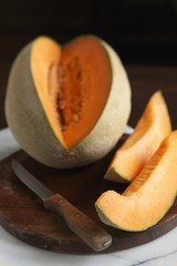 Cantaloupe with Two Wedges Cut Out; On Cutting Board with Knife