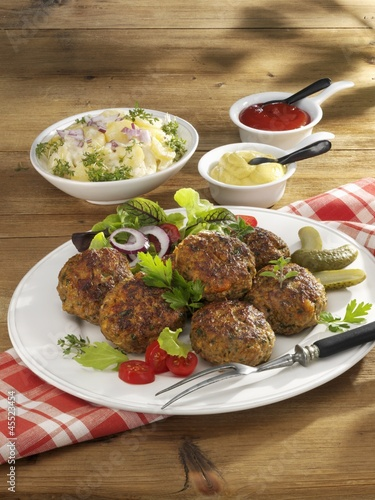 Meatballs with potato salad, mustard and ketchup