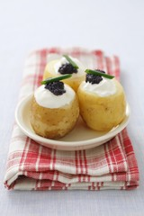 Potatoes topped with cream cheese and caviar