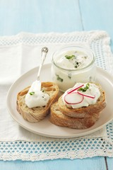 Slices of bread topped with chive quark and radishes