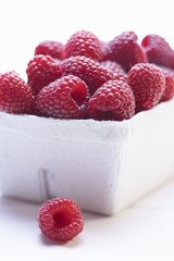 Raspberries in cardboard punnet (close-up)