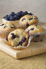 Four Blueberry Muffins on a Cutting Board with Fresh Blueberries; On Bitten