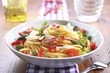 Spaghetti Tossed with Fresh Vegetables in a White Bowl with a Fork