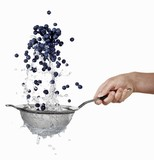 Blueberries being washed in a sieve