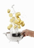 Peeled potatoes being washed in a sieve