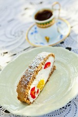 A slice of wholemeal sponge cake, filled with quark cream, mango and strawberries with a cup of mocha in the background
