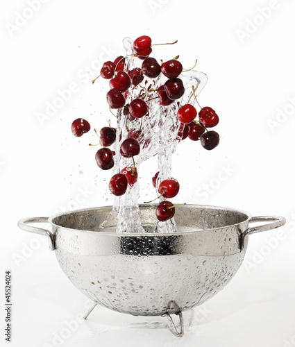 Cherries and a splash of water falling into a colander