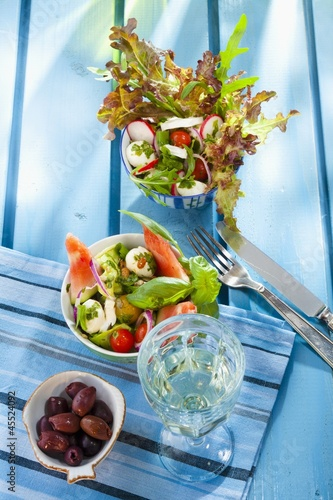 Two summer salads, olives and a glass of white wine