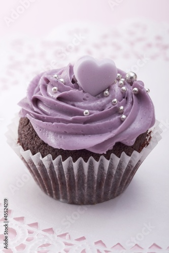 Chocolate cupcake with blackberry icing, silver balls and sugar heart