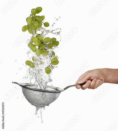 Washing green grapes in a sieve