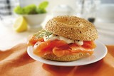 A sesame bagel with smoked salmon and mayonnaise