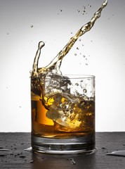 Ice cube falling into whisky glass