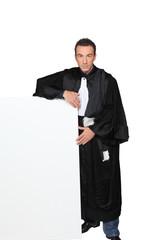 Man in fancy dress holding message board