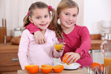 two little girls drinking orange juice