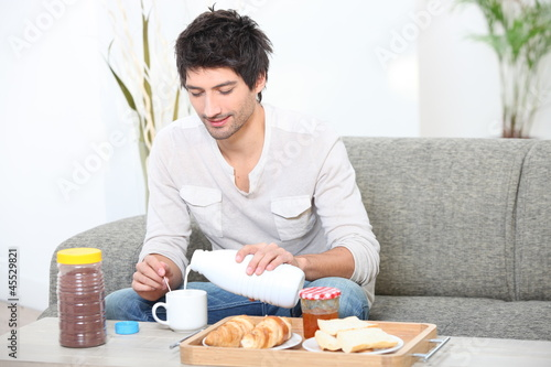 Young man having breakfast in his living room