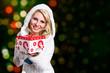 junge blonde Frau im Winteroutfit mit Geschenkbox