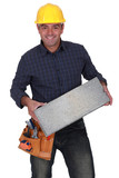 Cheerful builder with a concrete block