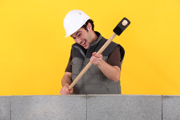 Construction worker destroying his work.