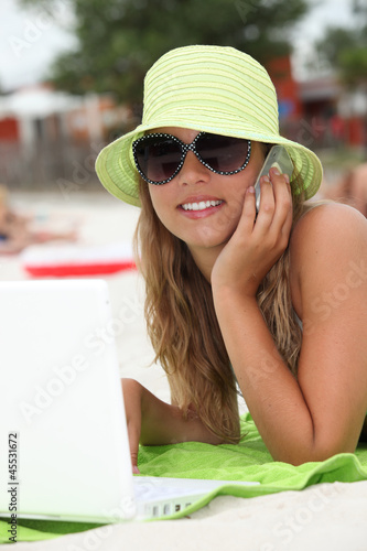 Young woman using technology on the beach