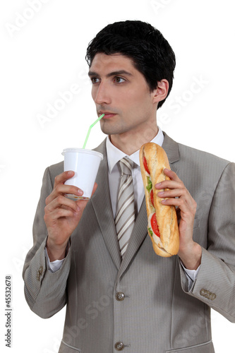 smart pensive businessman having quick lunch break