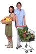 Market vs supermarket: Couple shopping for fruit and vegetables