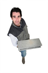 bricklayer standing with concrete block