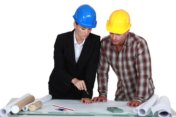 Two architects examining plans