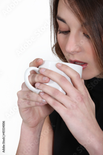 A brunette drinking coffee.