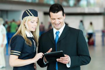 Freundlicher Businessmann und Stewardess analysieren etwas am Ta