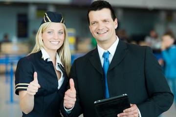 Stewardess und Business-Mann zeigen Daumen hoch