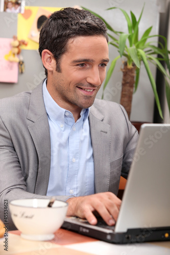 Man using his laptop during breakfast