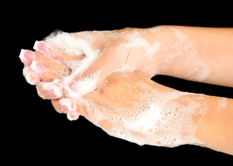 Woman's hands in soapsuds, on black background close-up