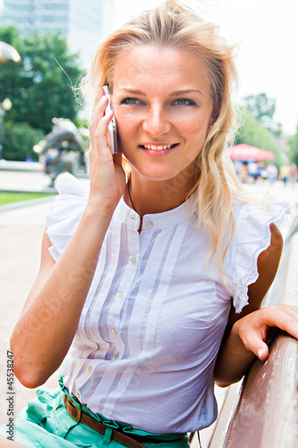 Young and beautiful woman talks on the phone while sitting on a