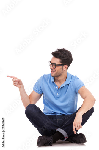 young man sitting and pointing sideways